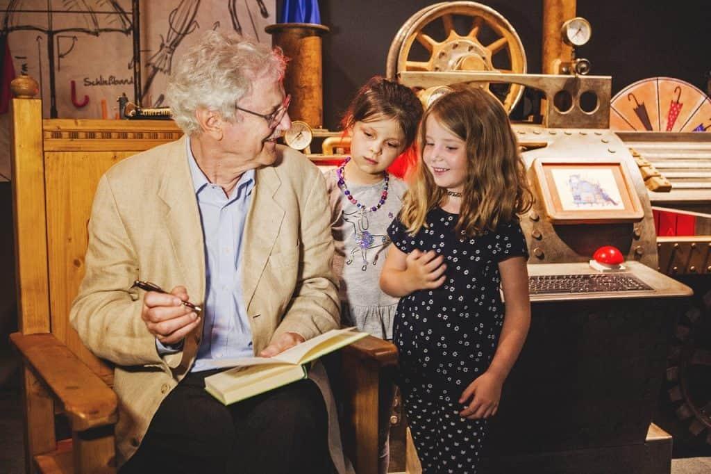 Paul Maar signierte in der Ausstellung seine Kinderbücher. Im Hintergrund ist die Regenschirmmaschine des Herrn Taschenbier zu sehen. Bildnachweis: Historisches Museum der Pfalz/Carolin Breckle