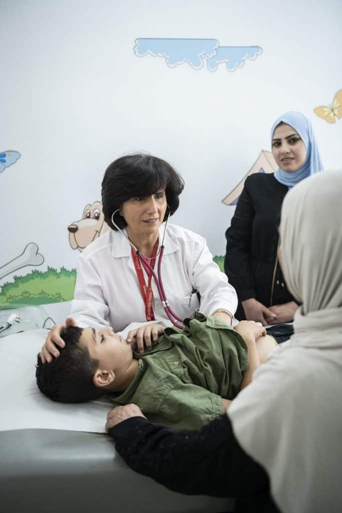 Dr. Hiyam Marzouqa untersucht im Ambulatorium einen jungen Patienten.